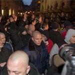 A MEASZ tüntetését megzavarók magasba emelik a karjukat Budapesten, az Új Színháznál