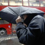 People shelter under an umbrella during heavy rain in central London