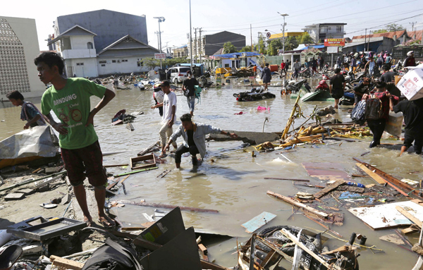 People survey the damage of the shopping mall following earthquakes and a tsunami in Palu, Central Sulawesi, Indonesia, Sunday, Sept. 30, 2018.  Rescuers try to reach trapped victims in collapsed buildings after hundreds of people are confirmed dead in a tsunami that hit two central Indonesian cities, sweeping away buildings with massive waves.(AP Photo/Tatan Syuflana)